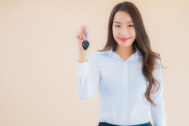 Retrato de mulher jovem e bonita asiática com chave de carro