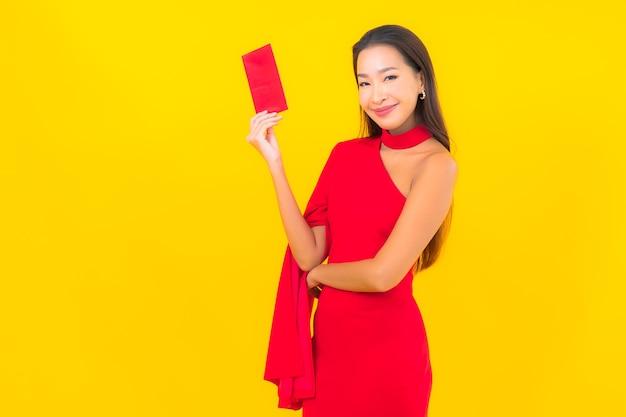 Retrato de mulher jovem e bonita asiática com envelope vermelho.