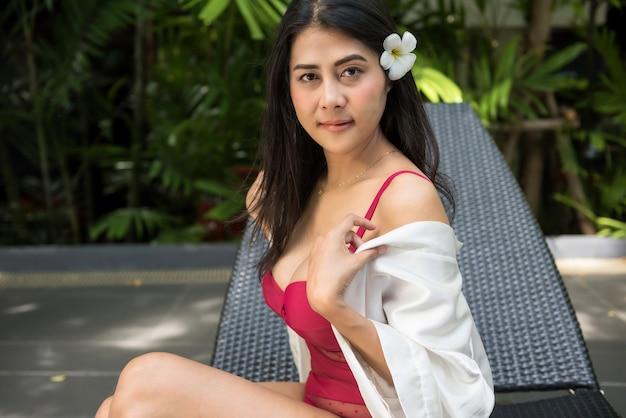 Retrato de mulher jovem e bonita asiática em maiô vermelho tirar o roupão de banho na cadeira da cama da piscina. garota atraente sensual relaxar no verão. conceito de férias e férias.