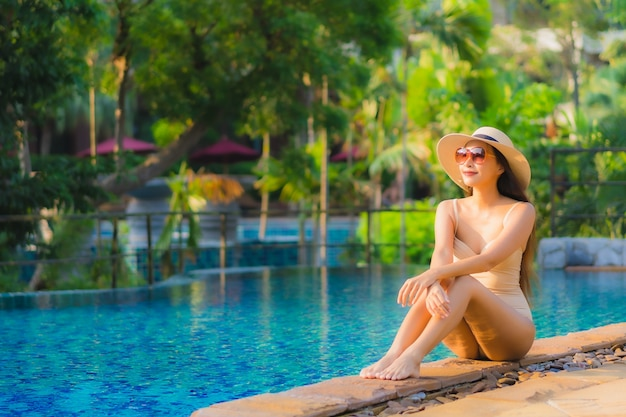 Retrato de mulher jovem e bonita asiática relaxa em torno da piscina no hotel resort