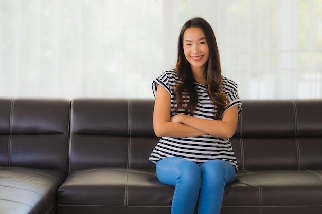 Retrato de mulher jovem e bonita asiática relaxa no sofá na sala de estar