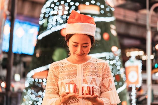Retrato de mulher jovem e bonita asiática sorridente com presente na feira festiva de natal