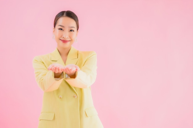 Retrato de mulher jovem e bonita asiática sorrindo em ação na cor rosa