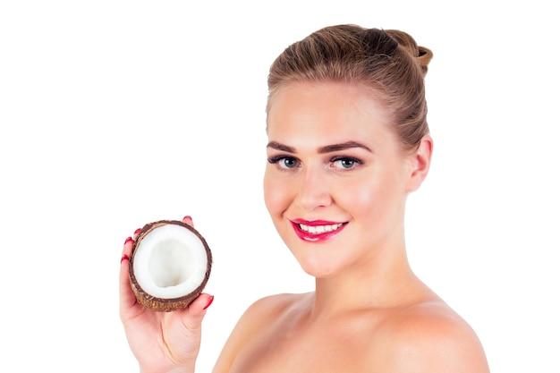 Retrato de mulher jovem e bonita com a pele perfeita segurando um coco no estúdio.