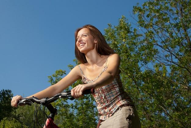 Retrato de mulher jovem e bonita com bicicleta em um parque sorrindo - ao ar livre