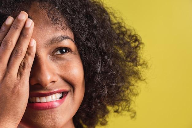 Retrato de mulher jovem e bonita com estilo afro em pé sobre fundo amarelo.