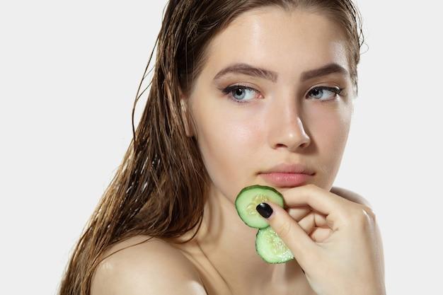 Retrato de mulher jovem e bonita com fatias de pepino fresco em fundo branco. conceito de cosméticos, maquiagem, tratamento natural e ecológico, cuidados com a pele. pele brilhante e saudável, moda, saúde.
