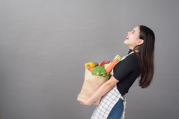 Retrato de mulher jovem e bonita com legumes na sacola de compras em fundo cinza studio