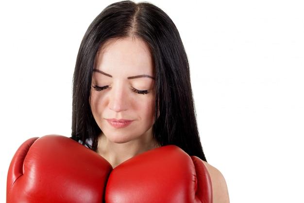 Retrato de mulher jovem e bonita com luvas de boxe e olhos fechados.