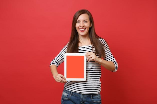 Retrato de mulher jovem e bonita com roupas listradas, segurando o computador tablet pc com tela vazia preta em branco isolada sobre fundo vermelho. conceito de estilo de vida de emoções sinceras de pessoas. simule o espaço da cópia.