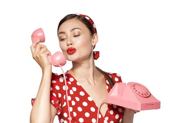 Retrato de mulher jovem e bonita com telefone, vestido em estilo pin-up.