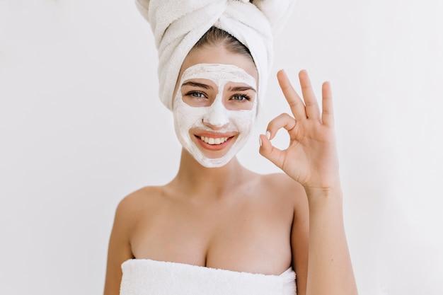 Retrato de mulher jovem e bonita com toalhas após o banho fazer máscara cosmética no rosto.