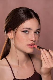 Retrato de mulher jovem e bonita com um produto de maquiagem