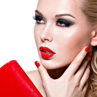 Retrato de mulher jovem e bonita com unhas e lábios vermelhos brilhantes. conceito - maquiagem de moda glamour