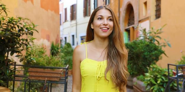 Retrato de mulher jovem e bonita com vestido de verão amarelo andando e explorando o bairro de trastevere, em roma, itália. vista panorâmica do banner.
