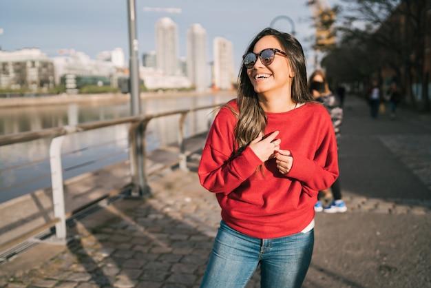 Retrato de mulher jovem e bonita confiante feliz e animado ao ar livre na rua.