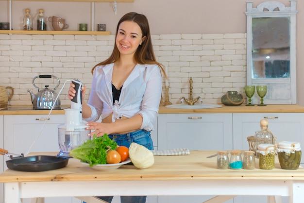 Retrato de mulher jovem e bonita cozinhando na cozinha. jovem mulher cozinhando. alimentos saudáveis - salada de vegetais.