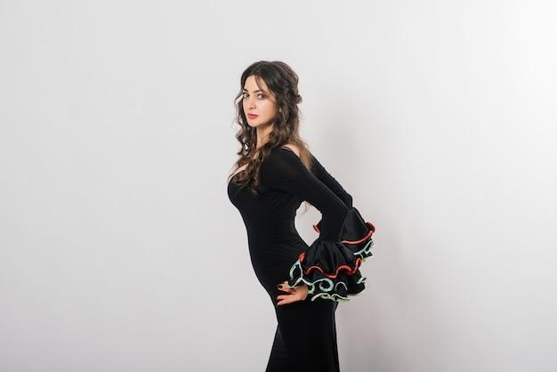 Retrato de mulher jovem e bonita dançando flamenco com ventilador no estúdio Foto Premium
