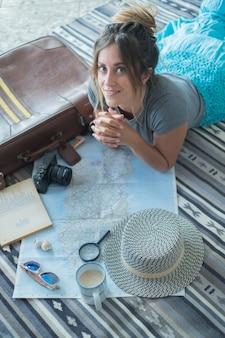 Retrato de mulher jovem e bonita deitada no tapete com uma xícara de café e atlas. jovem mulher planejando um local de férias no mapa com lupa. mulher planejando sua viagem com mapa, café, câmera