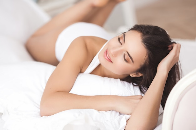 Retrato de mulher jovem e bonita dentro de casa. menina bonita fechar retrato. mulher adulta na cama branca.