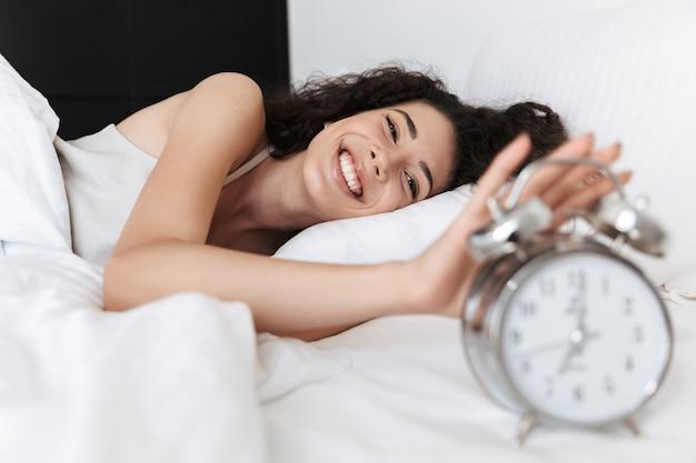Retrato de mulher jovem e bonita dormindo no quarto em casa e tocando o despertador na mesa de cabeceira com um sorriso