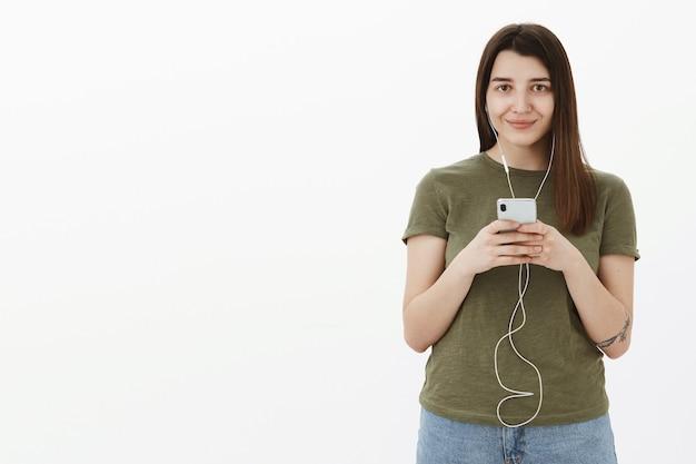 Retrato de mulher jovem e bonita dos 20 anos com uma tatuagem, sorrindo, encantada, segurando um smartphone e usando fones de ouvido com fio, ouvindo música na parede cinza