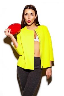 Retrato de mulher jovem e bonita elegante casaco amarelo com bolsa vermelha nas mãos, mostrando a língua