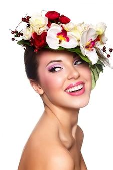 Retrato de mulher jovem e bonita elegante com flores coloridas na cabeça