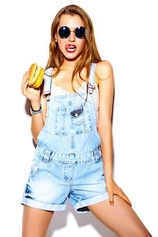 Retrato de mulher jovem e bonita elegante comendo hambúrguer