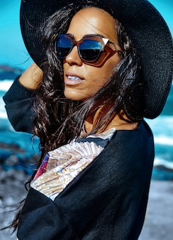 Retrato de mulher jovem e bonita elegante na praia