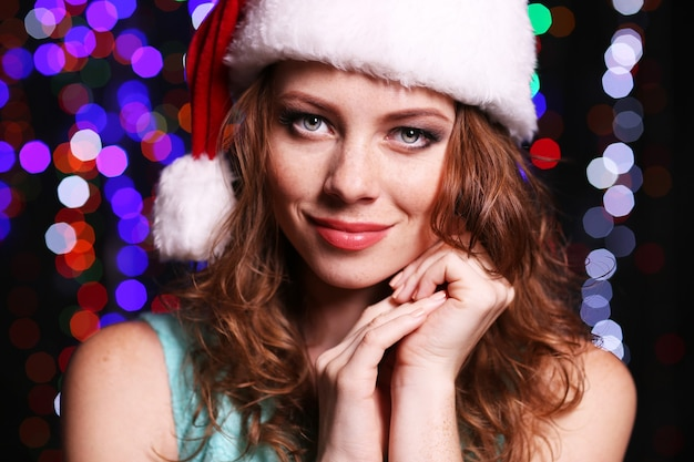 Retrato de mulher jovem e bonita em fundo de luzes brilhantes
