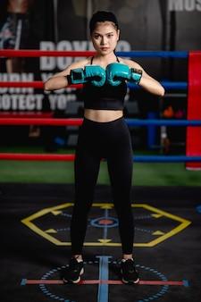 Retrato de mulher jovem e bonita em luvas de boxe em pé pose na tela no ginásio de fitness, aula de boxe de treino de menina saudável,