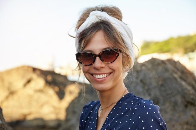 Retrato de mulher jovem e bonita em óculos de sol da moda vintage e bandana branca posando ao ar livre à beira-mar em dia de sol quente, olhando com um sorriso encantador