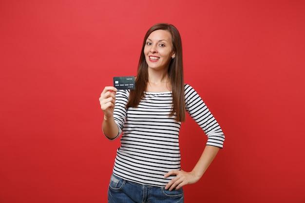 Retrato de mulher jovem e bonita em roupas listradas casuais, em pé e segurando o cartão de crédito isolado no fundo da parede vermelha brilhante. emoções sinceras de pessoas, conceito de estilo de vida. simule o espaço da cópia.