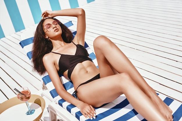 Retrato de mulher jovem e bonita em trajes de banho preto, deitada nas espreguiçadeiras perto da piscina. no verão, relaxe o conceito. gols corporais