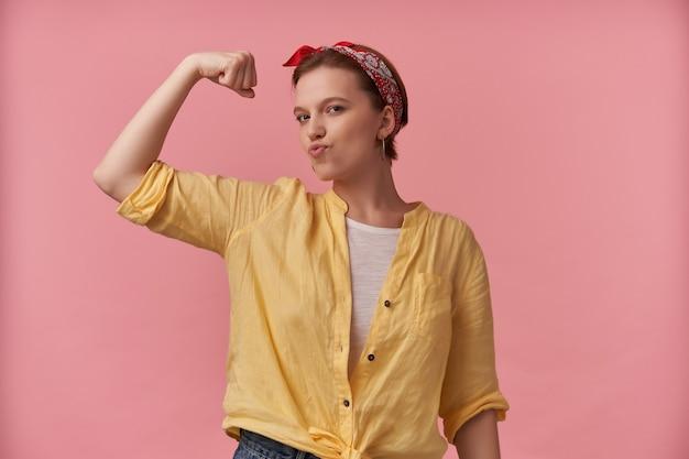 Retrato de mulher jovem e bonita em uma camisa amarela com bandana na cabeça parece forte e mostrando os músculos do bíceps sobre a parede rosa