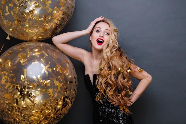 Retrato de mulher jovem e bonita em vestido de luxo preto, com cabelo loiro longo encaracolado, lábios vermelhos, com grandes balões cheios de enfeites dourados. celebração, espanto, positividade.