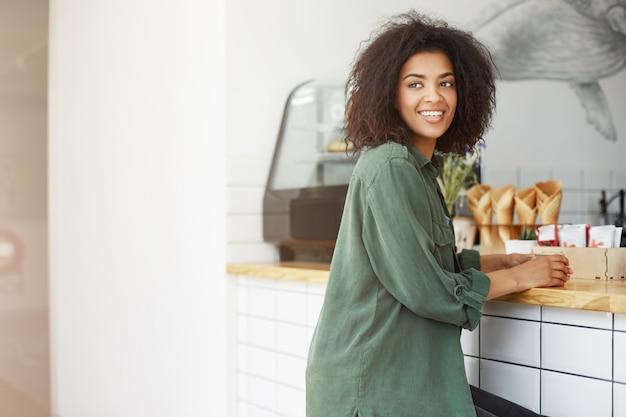 Retrato de mulher jovem e bonita estudante de pele grossa com cabelos cacheados em roupas da moda casuais, olhando de lado, sorrindo brilhantemente para um amigo lá fora, esperando seu pedido na cafeteria. vida