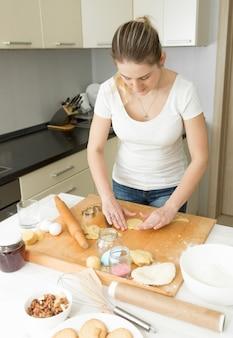 Retrato de mulher jovem e bonita fazendo massa na cozinha em casa
