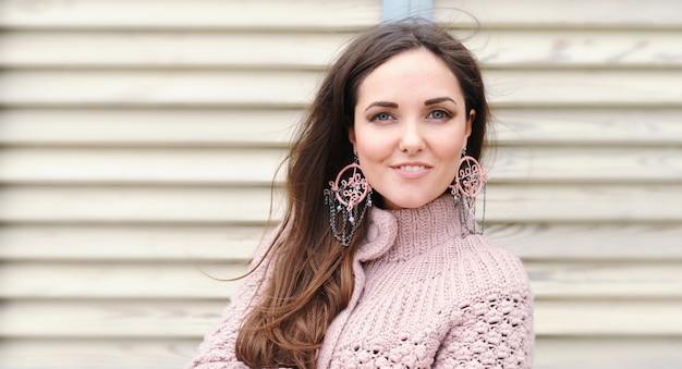 Retrato de mulher jovem e bonita feliz, suéter suave fofo e brincos estilo boho feitos à mão