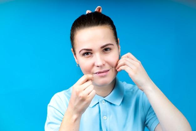 Retrato de mulher jovem e bonita feliz usando fio dental para limpar dentes saudáveis em azul