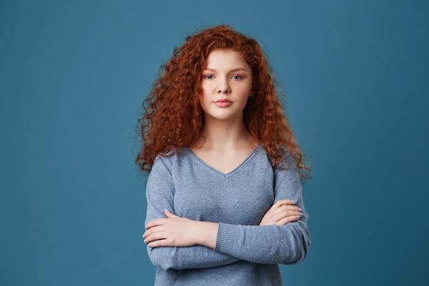 Retrato de mulher jovem e bonita gengibre com sardas cruzando as mãos, olhando com expressão relaxada e sorridente.