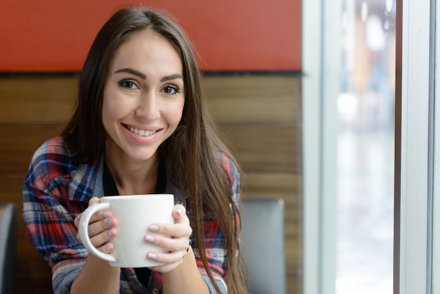 Retrato de mulher jovem e bonita hippie relaxando na cafeteria dentro de casa