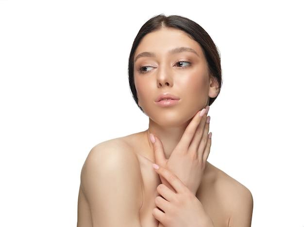 Retrato de mulher jovem e bonita isolada na parede branca. modelo feminino saudável caucasiano olhando para o lado, sério. conceito de saúde e beleza feminina, autocuidado, cuidados com o corpo e a pele.