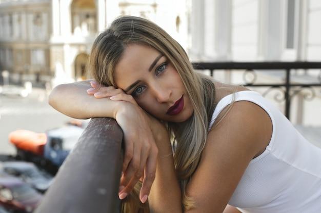 Retrato de mulher jovem e bonita loira que está deitado no corrimão com maquiagem diária leve, vestida com roupas brancas