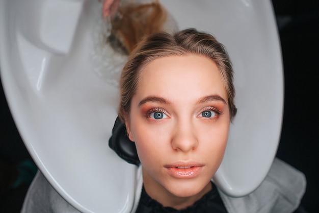 Retrato de mulher jovem e bonita loira sentada na pia branca