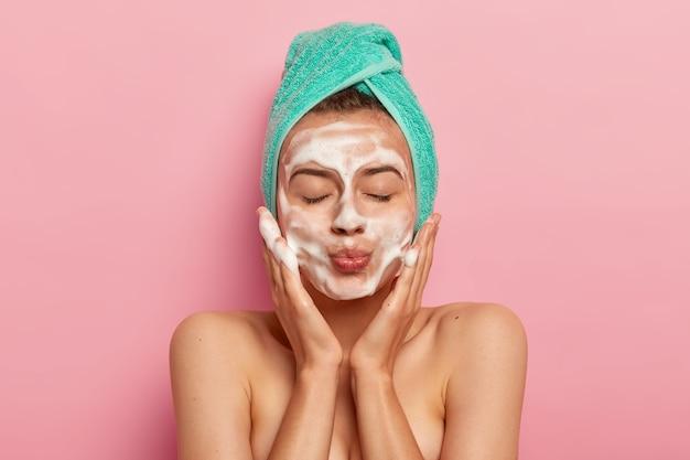 Retrato de mulher jovem e bonita mantém os lábios arredondados, olhos fechados, lava o rosto com gel espumante, massageia as bochechas, usa toalha turquesa, gosta de tratamentos de higiene no banheiro, começa um novo dia