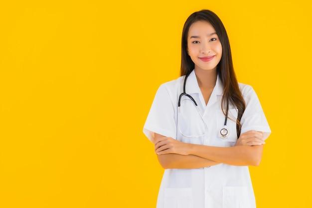 Retrato de mulher jovem e bonita médico asiático sorrir feliz