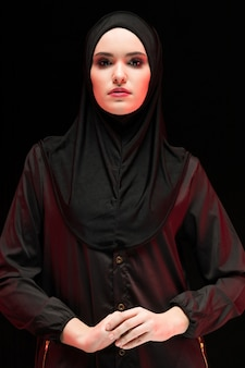 Retrato de mulher jovem e bonita muçulmana vestindo preto hijab