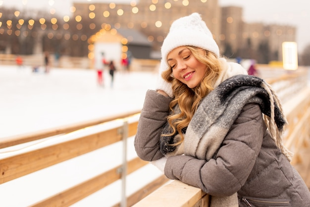 Retrato de mulher jovem e bonita na fila de gelo do natal festivo. senhora vestindo roupas de malha quentes de inverno.